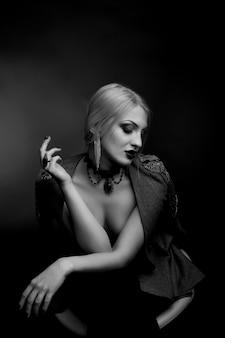 Stylowy czarno-biały portret studyjny pięknej kobiety z jasnym makijażem noszącej kurtkę na nagim ciele