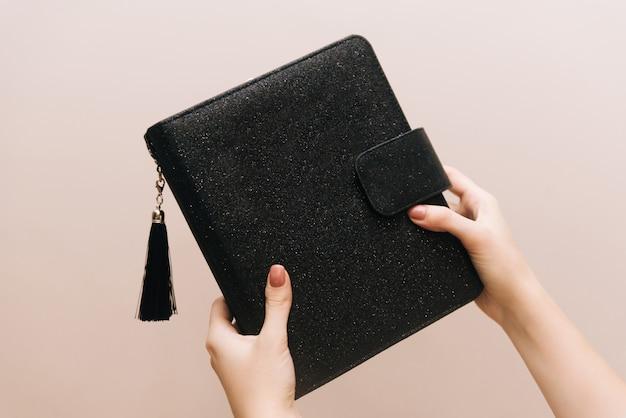 Stylowy czarny notatnik z pędzelkiem i guzikiem w rękach dziewczynki. wolne miejsce na logo