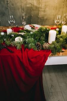 Stylowy czerwony stół z płonącymi świecami i świątecznymi dekoracjami na szarej powierzchni
