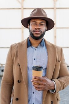 Stylowy człowiek african american, trzymając filiżankę kawy