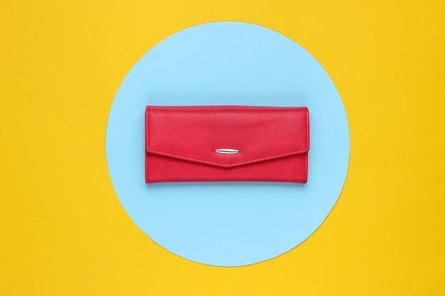 Stylowy damski portfel skórzany w kolorze czerwonym na żółtym tle w pastelowe niebieskie kółko. kreatywna minimalistyczna moda martwa. widok z góry