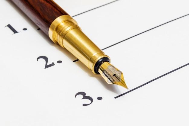 Stylowy długopis leży na kartce z numerami jeden, dwa i trzy
