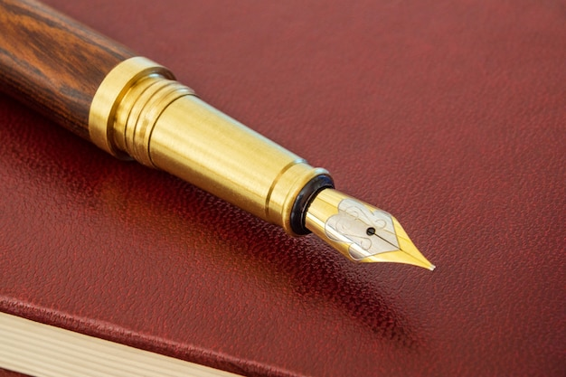 Stylowy długopis z pozłacanym długopisem na brązowym notatniku na notatki