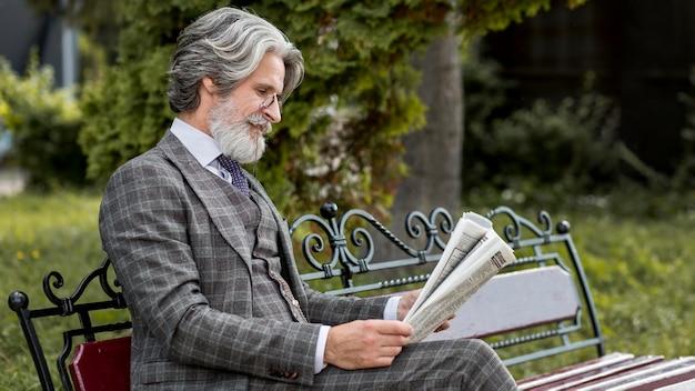 Stylowy dojrzały mężczyzna czyta gazetę na świeżym powietrzu