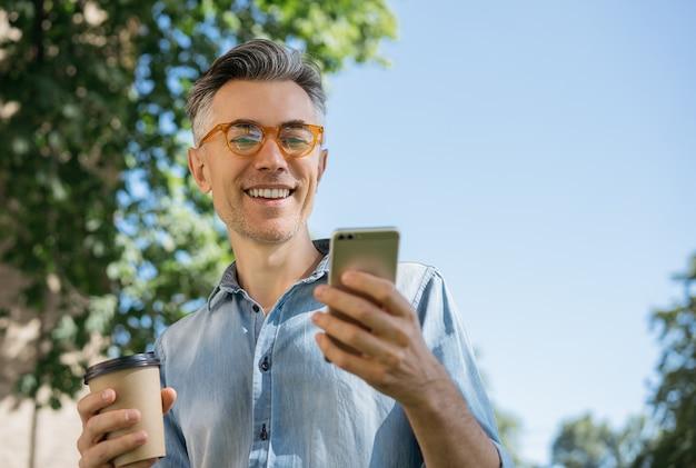 Stylowy dojrzały mężczyzna za pomocą telefonu komórkowego