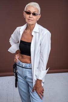 Stylowy dorosły. miła kobieta ubrana w nowoczesny strój podczas kręcenia w studio