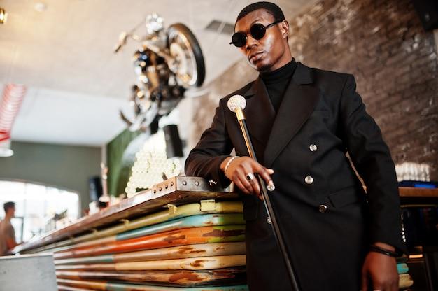 Stylowy dżentelmen w eleganckiej czarnej kurtce i okularach przeciwsłonecznych, trzymający laskę retro jako kolbę trzciny cukrowej