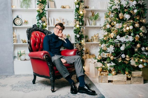 Stylowy, elegancki mężczyzna siedzi na krześle w pobliżu drzewa cristmas w studio z nowymi dekoracjami.