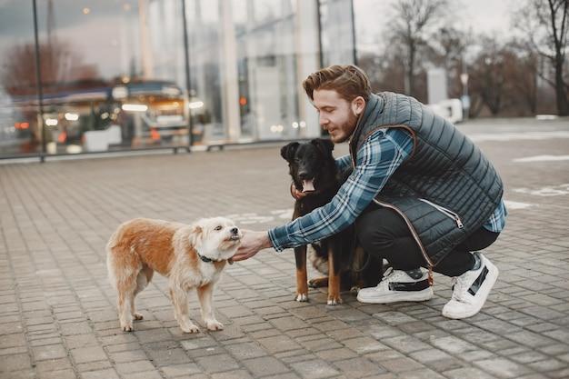 Stylowy facet bawi się z psami. mężczyzna w mieście jesienią.