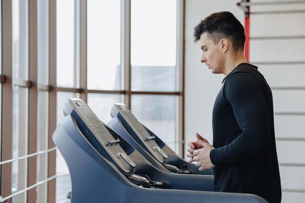 Stylowy facet na siłowni trenuje na bieżni. zdrowy tryb życia.
