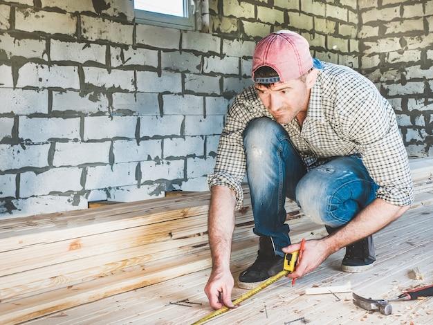 Stylowy facet w czapce z daszkiem, dżinsach i koszuli, pracujący narzędziami na drewnie wewnątrz budowanego domu. koncepcja budowy i naprawy