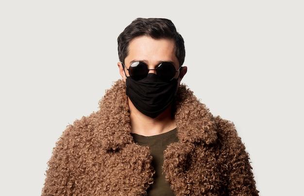 Stylowy facet w jodłowym płaszczu z okularami przeciwsłonecznymi i maską na twarz