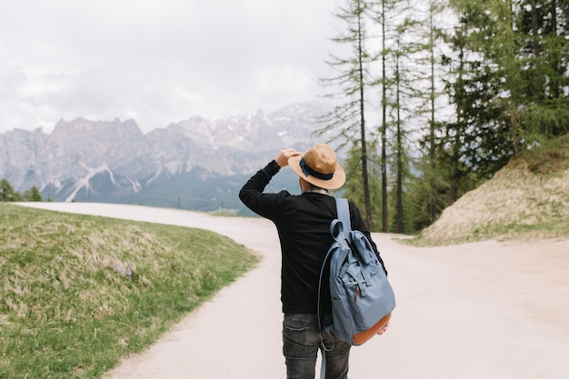 Stylowy facet w kapeluszu podziwia górską scenerię spędzając czas na świeżym powietrzu w wiosenne wakacje