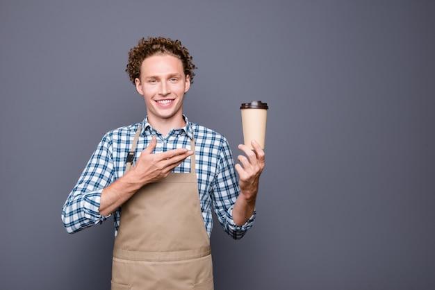 Stylowy facet w kraciastej koszuli i fartuchu, pozujący na szarej ścianie