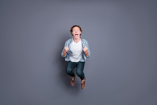 Stylowy facet w niebieskiej koszuli w kratkę pozujący na szarej ścianie