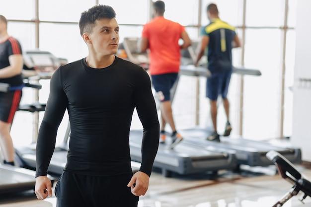 Stylowy facet w siłowni pozuje do zdjęcia. zdrowy tryb życia.