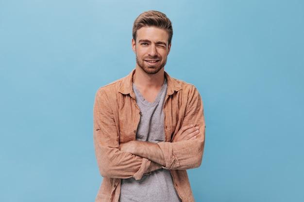 Stylowy facet z brodą w brązowej koszuli i koszulce uśmiechający się i mrugający na odosobnionej ścianie. fajny mężczyzna pozujący na niebieskiej ścianie