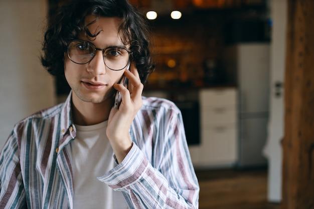 Stylowy facet z kręconymi włosami pozuje do przytulnego wnętrza kuchni po rozmowie telefonicznej za pomocą telefonu komórkowego