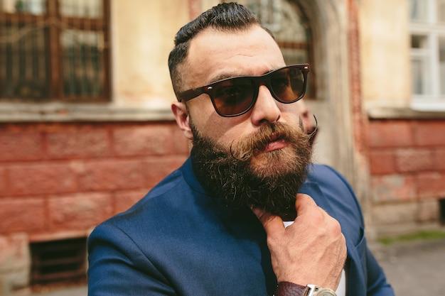Stylowy fajny brodaty mężczyzna na tle starego miasta