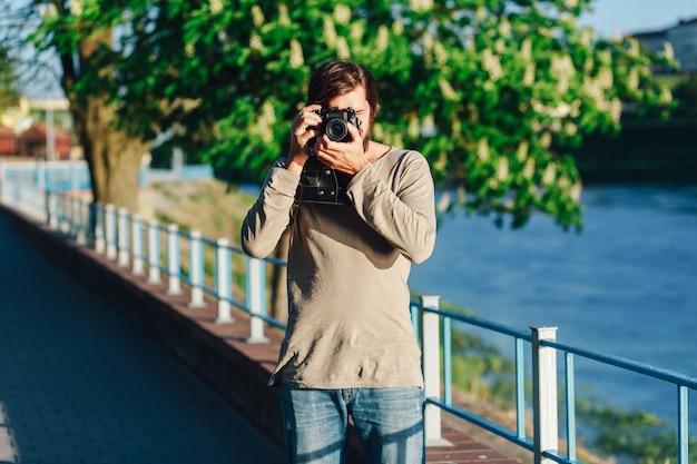 Stylowy fotograf spacerujący po mieście z retro aparatem fotograficznym