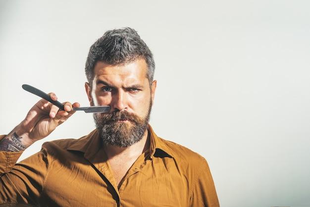 Stylowy fryzjer z niebezpieczną brzytwą do golenia w studio brodaty przystojny seksowny macho z prostą