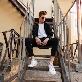 Stylowy hipster mężczyzna w okularach przeciwsłonecznych w czarnej koszuli w tshirt w eleganckich pasiastych spodniach w trampkach siedzi na żelaznych schodach w stylu vintage