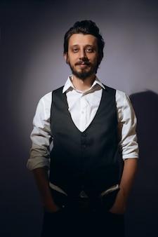 Stylowy hipster mężczyzna z brodą stoi w ścianie w kamizelce i białej koszuli