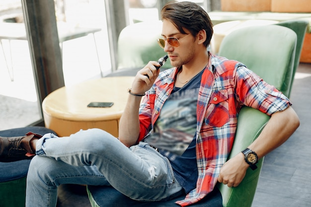 Stylowy i elegancki mężczyzna siedzący w kawiarni z vape