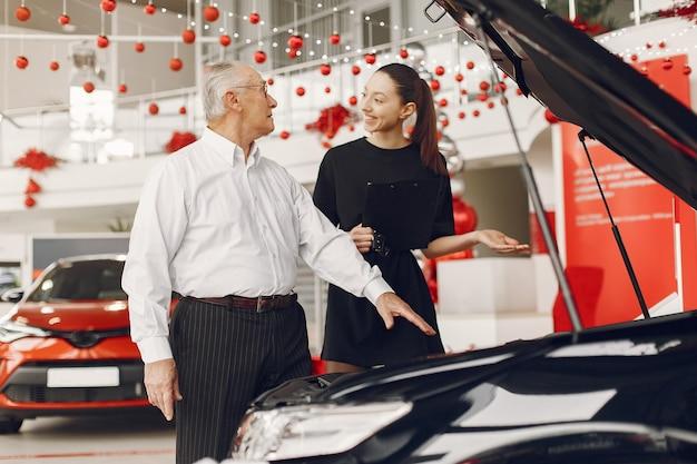 Stylowy i elegancki starzec w salonie samochodowym