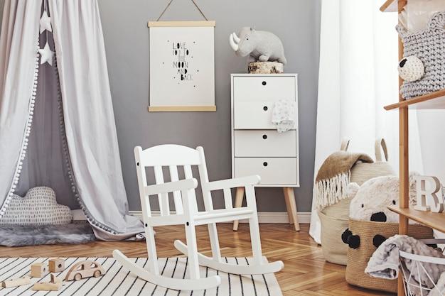Stylowy i jasny skandynawski wystrój pokoju noworodka z plakatem, białymi designerskimi meblami, naturalnymi zabawkami, wiszącym szarym baldachimem z drewnianą kołyską, regałem, akcesoriami i pluszami