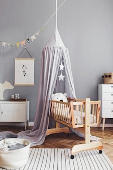 Stylowy i jasny skandynawski wystrój pokoju noworodka z plakatem, białymi designerskimi meblami, naturalnymi zabawkami, wiszącym szarym baldachimem z drewnianą kołyską, regałem, akcesoriami i pluszowymi misiami