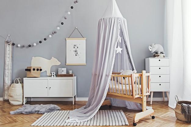 Stylowy i jasny skandynawski wystrój pokoju noworodka z plakatem, białymi designerskimi meblami, naturalnymi zabawkami, wiszącym szarym baldachimem z drewnianą kołyską, regałem i akcesoriami