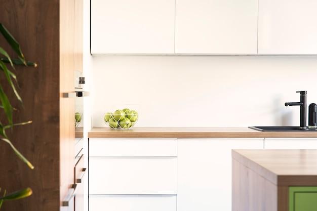 Stylowy i kreatywny projekt wnętrza kuchni z miejscem do pracy, stołem jadalnym, krzesłami i akcesoriami kuchennymi. nowoczesny styl. jasna i przestronna przestrzeń. zielony kolor. wiosenne wibracje.