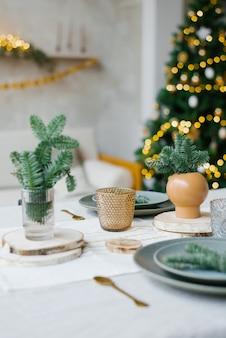 Stylowy i modny design świątecznego nakrycia stołu na rodzinny obiad. wazony ze świerkowymi gałązkami, szklankami i talerzami na tle lampek choinkowych