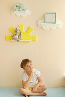 Stylowy i nowoczesny wystrój wnętrz. dom do pokoju dziecka. dziecko raduje się w odnowionym pokoju. półki dziecięce w formie białych chmurek na gładkiej beżowej ścianie z ramką na zdjęcia.