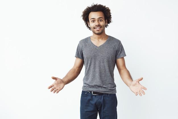 Stylowy i przystojny afrykański mężczyzna z szeroko otwartymi ramionami przy białej ścianie zaprasza na koncert.