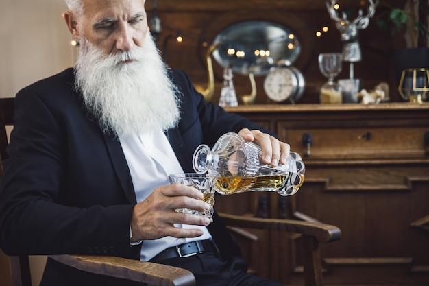 Stylowy i przystojny brodaty starszy mężczyzna ze szklanką whisky
