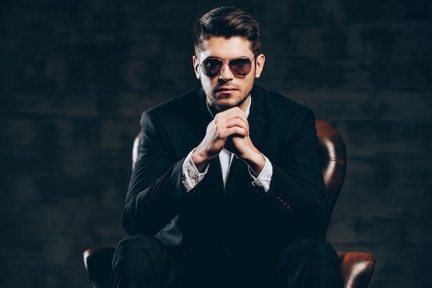 Stylowy i udany. młody przystojny mężczyzna w garniturze i okularach przeciwsłonecznych trzymając ręce splecione i patrząc na kamerę siedząc w skórzanym fotelu na ciemnoszarym tle