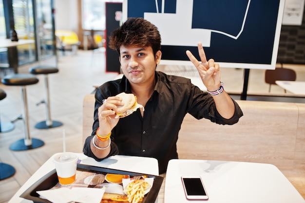 Stylowy indyjski mężczyzna siedzący w kawiarni fast food i jedzenie hamburgera i gest dłoni znak pokoju.