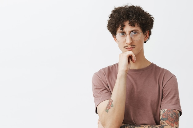 Stylowy, inteligentny i kreatywny młodzieniec z wąsami i tatuażami na ramionach w okularach myśli o pocieraniu podbródka i poważnym spojrzeniu