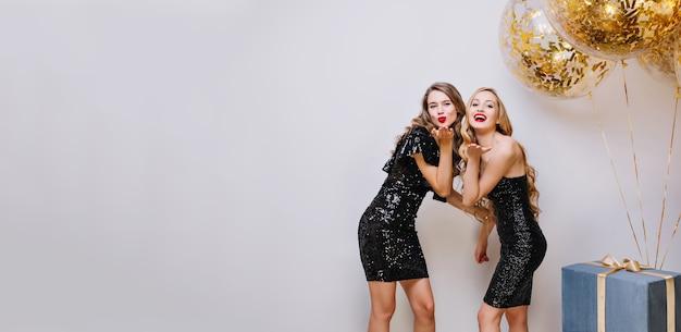 Stylowy, jasny obraz dwóch radosnych atrakcyjnych kobiet świętujących imprezę w luksusowych czarnych sukienkach na białej przestrzeni