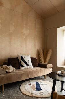 Stylowy kącik dzienny z sofą w kolorze aksamitnej opalenizny z miękkimi poduszkami ze ścianą ze sklejki w tle / przytulny wystrój wnętrza / nowoczesne wnętrze