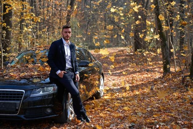 Stylowy kaukaski mężczyzna biały garnitur w pobliżu samochodu jesieni