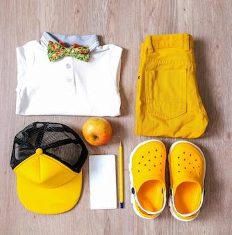 Stylowy komplet małego chłopca z dominującymi żółtymi kolorami i dodatkami.