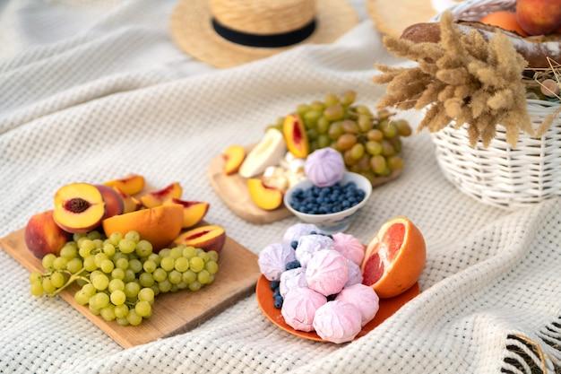 Stylowy letni piknik na białym kocu.
