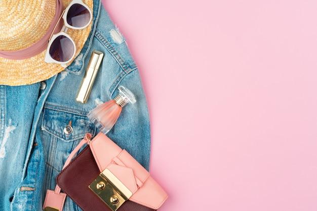 Stylowy letni strój dla kobiety na pastelowym różowym tle