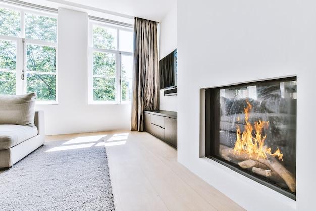 Stylowy, luksusowy projekt wnętrza przytulnego salonu z płonącym kominkiem i wygodną sofą i dywanem w świetle dziennym