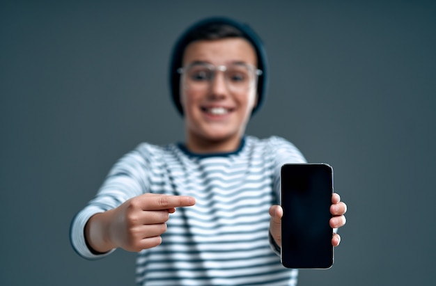 Stylowy mądry uczeń w kapeluszu i okularach pokazuje palec na smartfonie na białym tle na szarym tle.