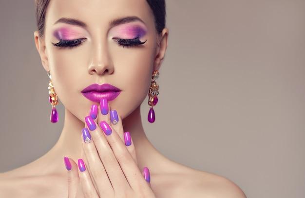 Stylowy makijaż w odcieniach fioletu, nieskazitelne czarne rzęsy i ładnie wymodelowane usta pomalowane na fioletowo