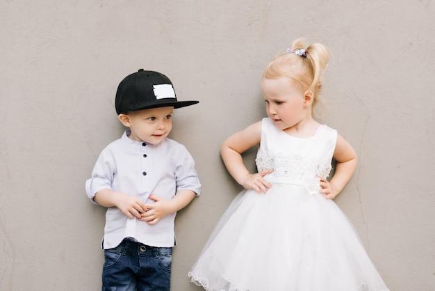 Stylowy mały chłopiec i dziewczynka na szarej ścianie